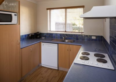 Fully equipped kitchen with stove, hot plates, fridge, microwave, dishwasher, electric toaster, kettle, cooking utensils, glasses, plates. Separate laundry.